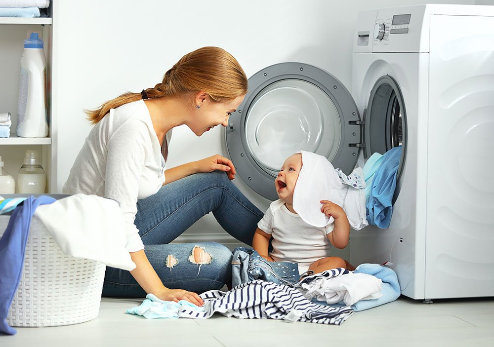 Woman doing laundry with baby